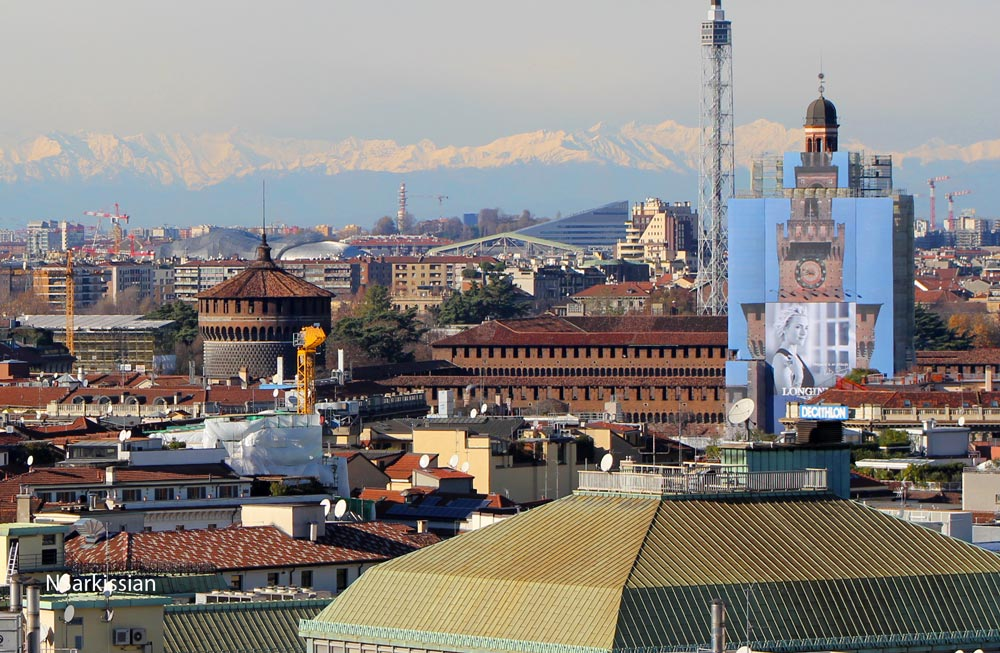 The Sforza Castle (also under restoration) in the middleground, snow-capped Alps on the horizon
